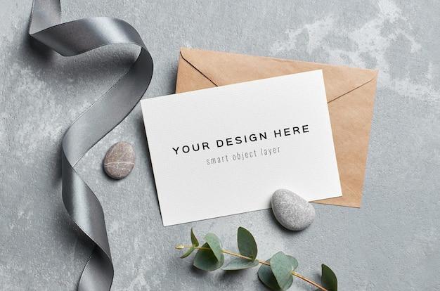 ユーカリの小枝と灰色の石でスタイリッシュな結婚式のグリーティングカードのモックアップ