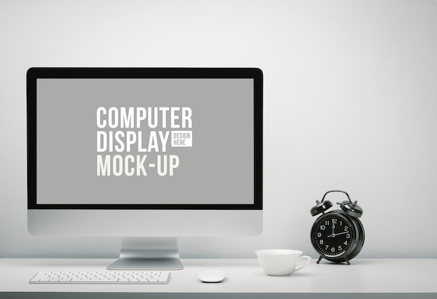 Stylish workspace with blank screen computer display for mockup on work desk with keyboard, mouse, cup of coffee and clock. copy space on wall for text.