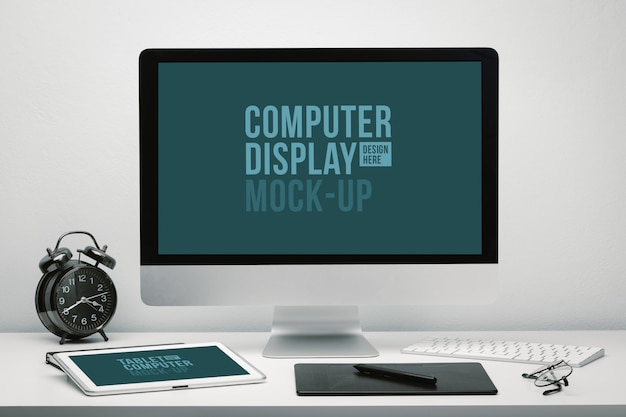 Stylish workspace with blank screen computer display and tablet for mockup on work desk with keyboard, mouse, clock, eyeglasses and pen tablet.