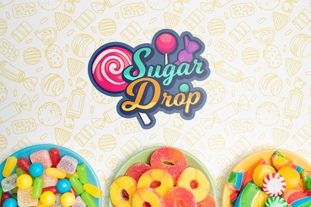 Сахарная капля и тарелки с вкусным ассортиментом конфет