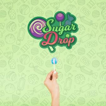 손으로 설탕 드롭 및 녹색 배경 낙서