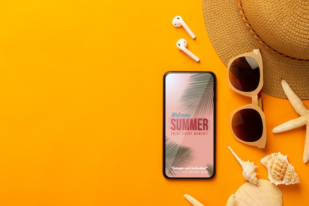 Summer background with phone mockup template and beach accessories on vibrant orange background