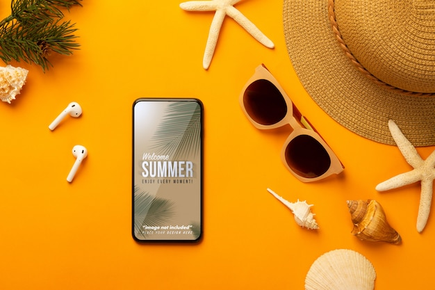 Summer background with phone mockup template and beach accessories on vibrant orange