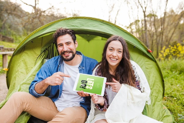 Summer camp mockup with couple pointing at tablet
