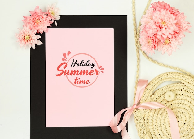 Summer composition with black frame, pink flowers and straw bag on white background