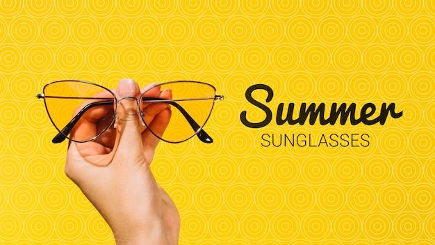 Летние модные солнцезащитные очки держат в руках