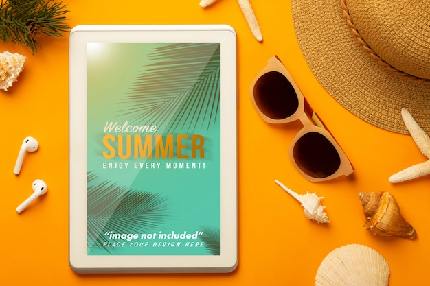 Summer scene with tablet mockup and beach accessories