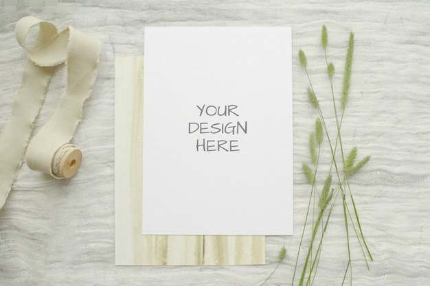 Summer stationery mockup ard for greeting card or wedding invitation with herbs, vintage spool of cotton braid on white Premium Psd