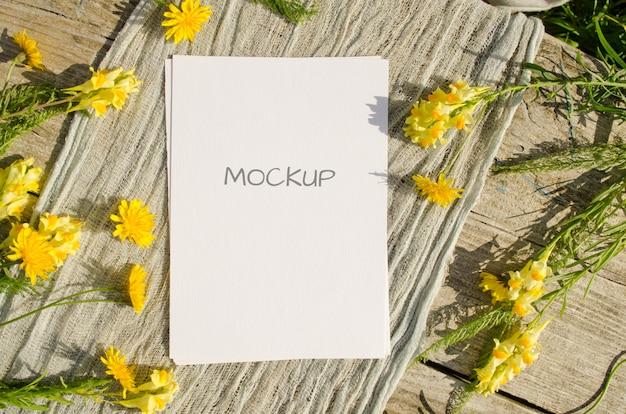 소박한 스타일과 자연의 오래 된 나무 공간에 노란색 꽃과 여름 편지지 모형 인사말 카드 또는 청첩장