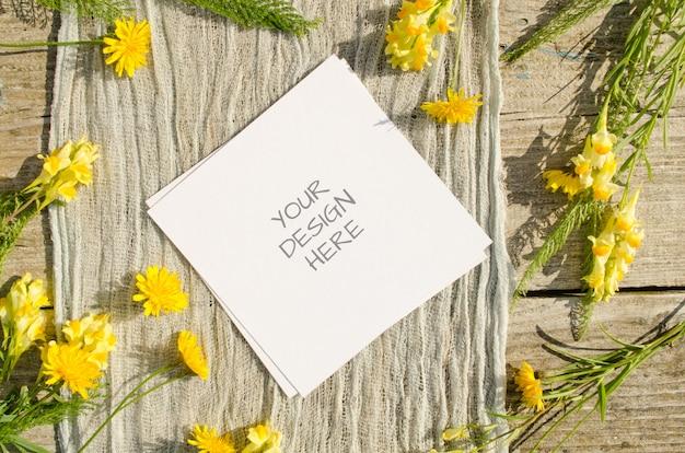 夏の文房具モックアップグリーティングカードまたは素朴なスタイルと自然の古い木製のスペースに黄色い花を持つ結婚式の招待状