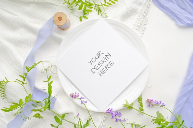 Summer stationery mockup greeting card or wedding invitation with violet flowers and delicate silk ribbons on a white space