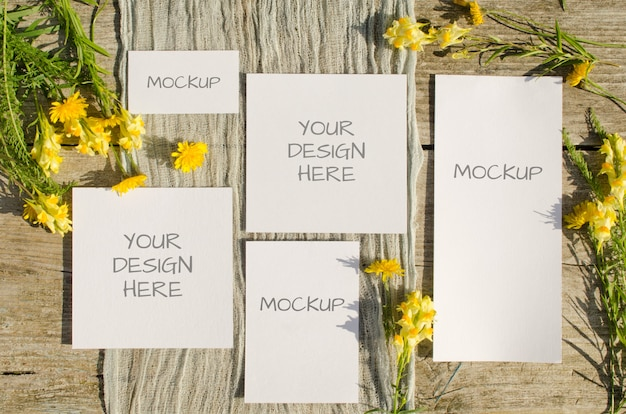 Summer stationery mockups set scene with with yellow flowers on old wood