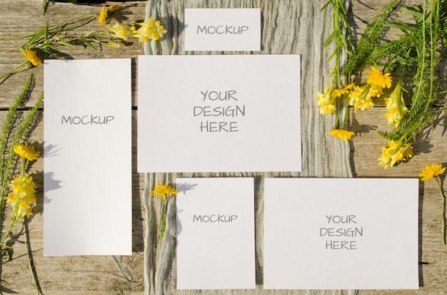 夏の文房具weddindモックアップは古い木の黄色い花を持つカードを設定
