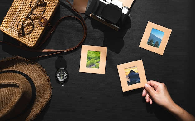 Summer travel of traveller accessories set.hand pick up picture frame on black wooden table