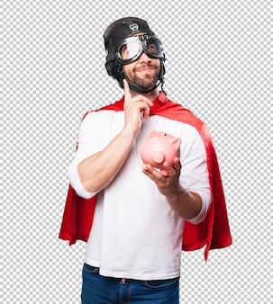 Super hero holding a piggy bank