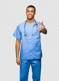 Surgeon doctor man smiling and showing victory sign