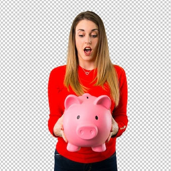 Surprised young blonde woman holding a piggybank