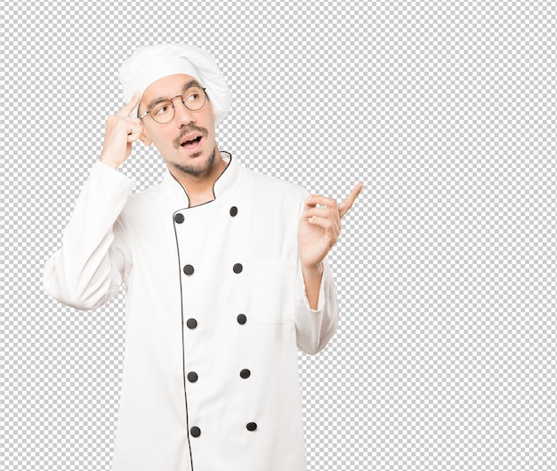 Surprised young chef doing a gesture of concentration