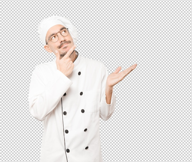 Surprised young chef making a gesture of doubt