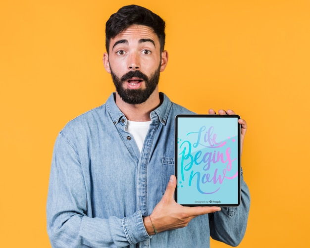 Surprised young man holding a tablet mock up