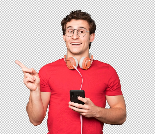 Surprised young man using a smartphone and pointing with his finger