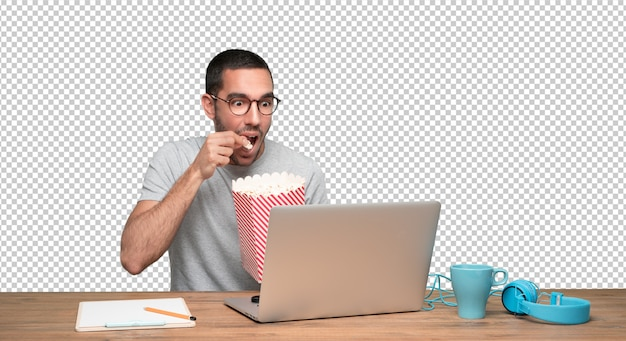 Surprised young man watching a film on his laptop and eating popcorn
