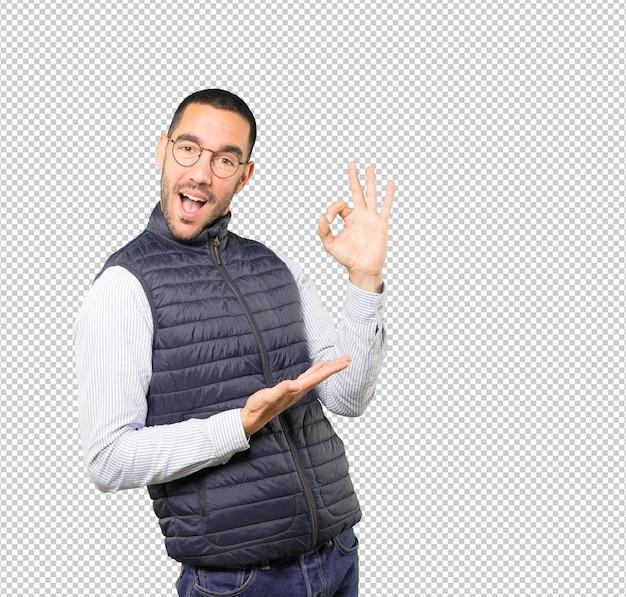 Удивленный молодой человек с жестом одобрения