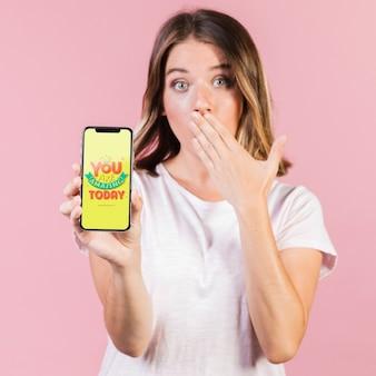 驚いた若い女性が彼女の口を覆っていると携帯電話のモックアップを保持