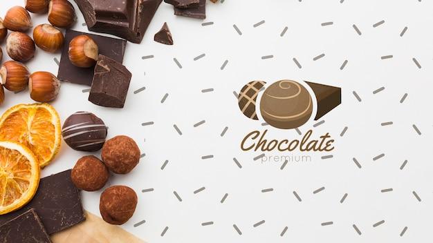 Cioccolato zuccherato e frutti con il modello bianco del fondo