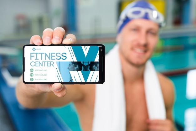 Пловец держит мобильный телефон с целевой страницей в фитнес-центре