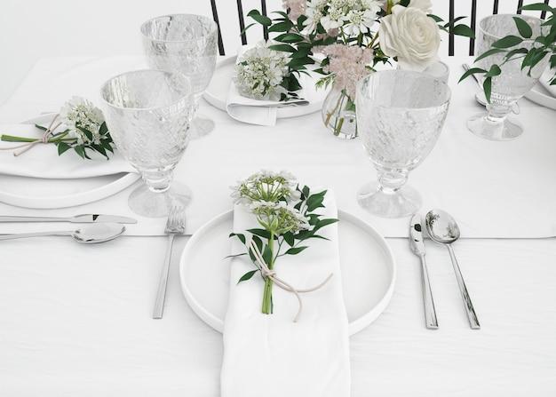 Стол, приготовленный для еды со столовыми приборами и декоративными цветами