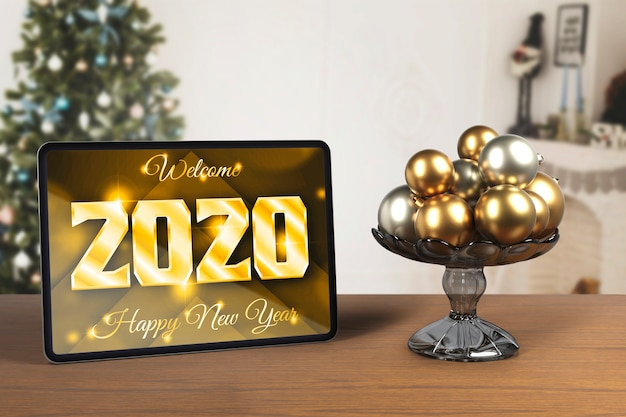 Tablet beside tray with globes for new year