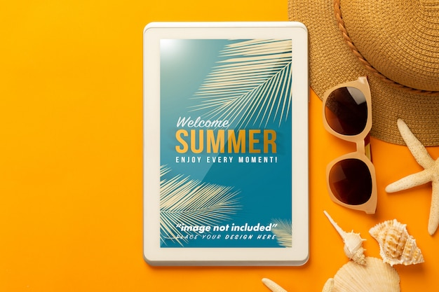 Tablet computer mockup template and beach accessories on orange