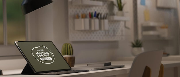 Tablet on desk low light from table lamp with modern work space designed in white and copy space