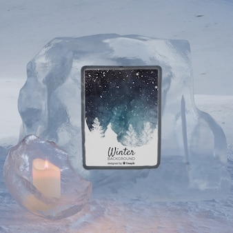 Tablet on ice block light by candle
