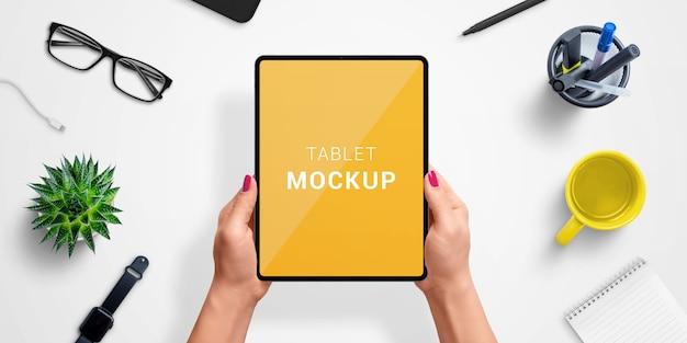 アプリやwebサイトのデザインプレゼンテーションのモックアップのための隔離された画面で女性の手でタブレットします。トップビュー、フラットレイアウト構成