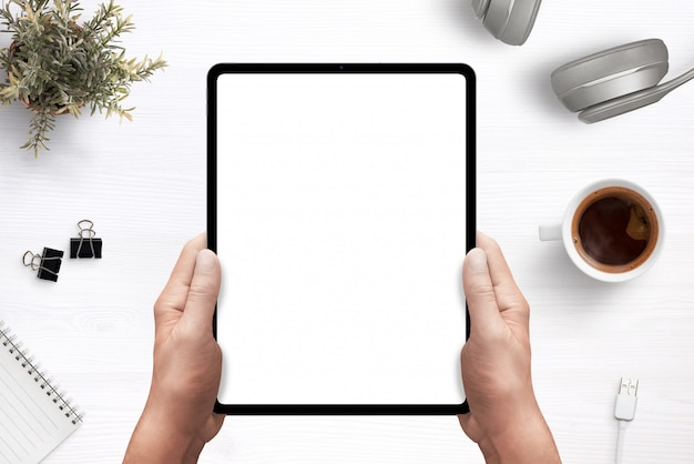 Tablet in man hands mockup above work desk with separated layers for creating a scene