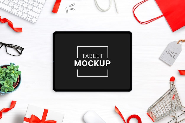 Tablet mockup on desk with shopping items