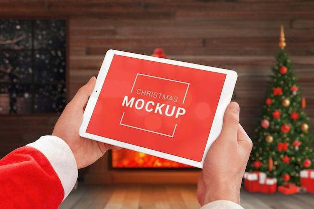 クリスマスの装飾が施された手でタブレットのモックアップ