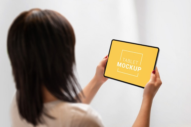 Планшет макет в руках женщины. посмотрите на планшет через плечо.