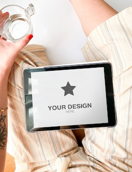 Tablet mockup on lap of a woman with summer clothes