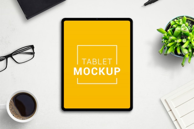 オフィスの机の上のタブレットのモックアップ。アプリやwebサイトのデザインプロモーションのための隔離された画面。レイヤーが分離されたシーン作成者