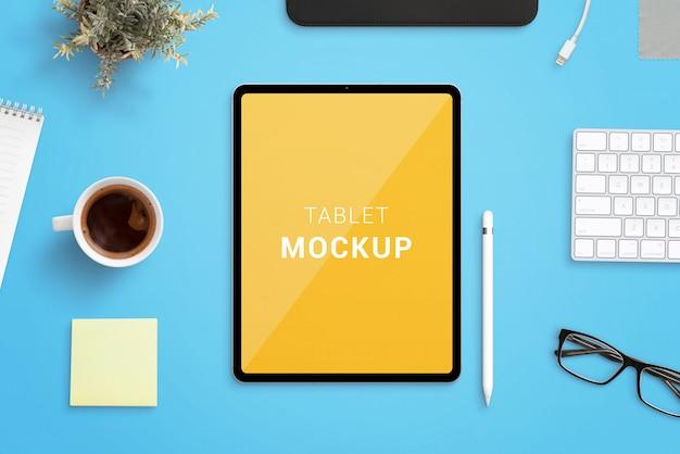 펜, 커피, 키보드, 식물, 패드 및 안경 컵으로 둘러싸인 사무실 책상에 태블릿 이랑. 둥글고 얇은 모서리가있는 최신 태블릿