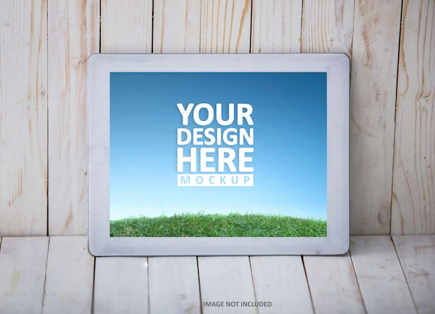 Tablet pc on the wall and wooden background, mockup