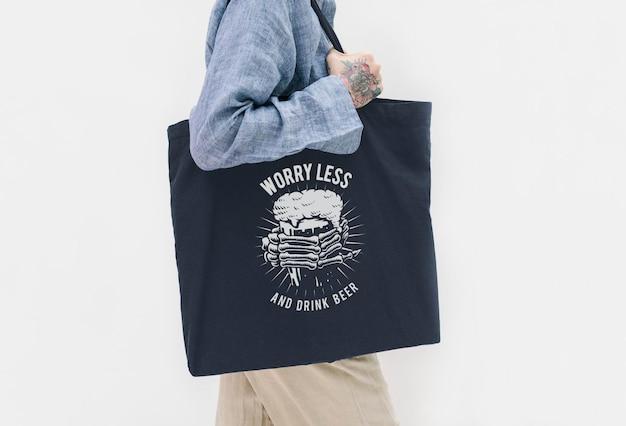 Donna tatuata con una camicia di lino blu con in mano una borsa nera