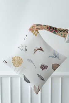 Tattooed woman holding a leafy pillow mockup