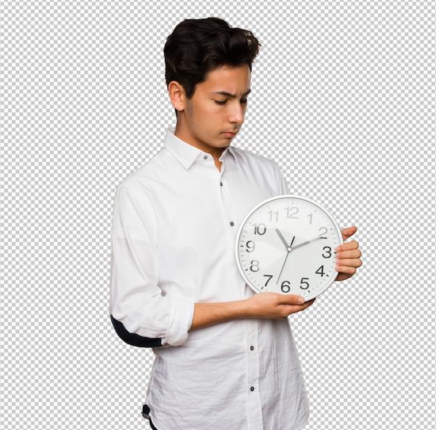 Teenager holding a big clock