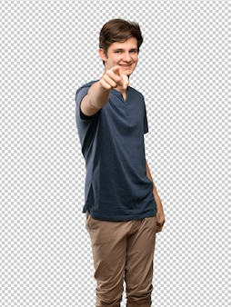 Teenager man points finger at you with a confident expression