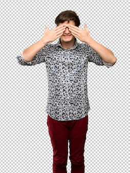 Teenager man with flower shirt and glasses covering eyes by hands. surprised to see what is ahead