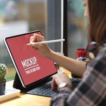 コーヒーショップのバーでモックアップデジタルタブレットを使用しているティーンエイジャー